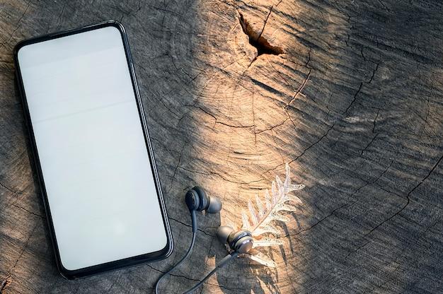 Modell smartphone mit weißem leerem bildschirm und kopfhörer auf hölzernem hintergrund. Premium Fotos