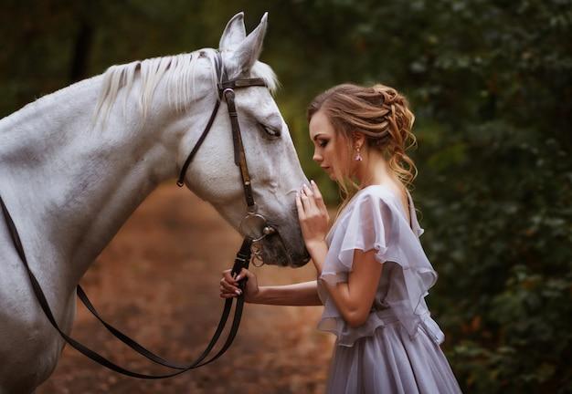 Modell und das weiße pferd schauen sich an. porträt. hintergrund verschwommen, künstlerische wirkung. Premium Fotos