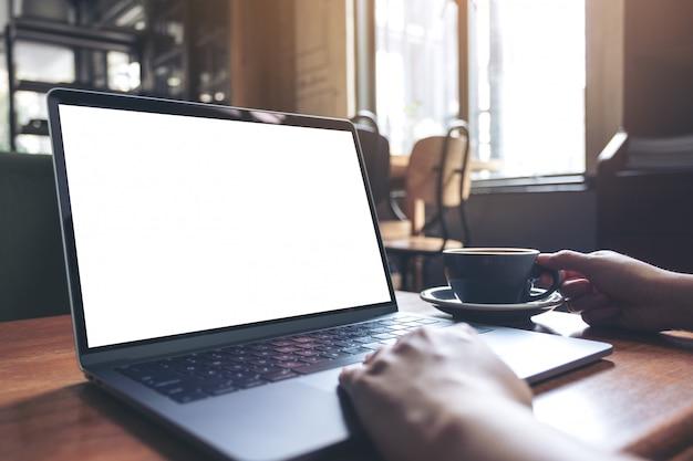 Modellbild einer frau, die laptop mit leerem weißen desktop-bildschirm beim trinken von heißem kaffee auf holztisch im café verwendet Premium Fotos