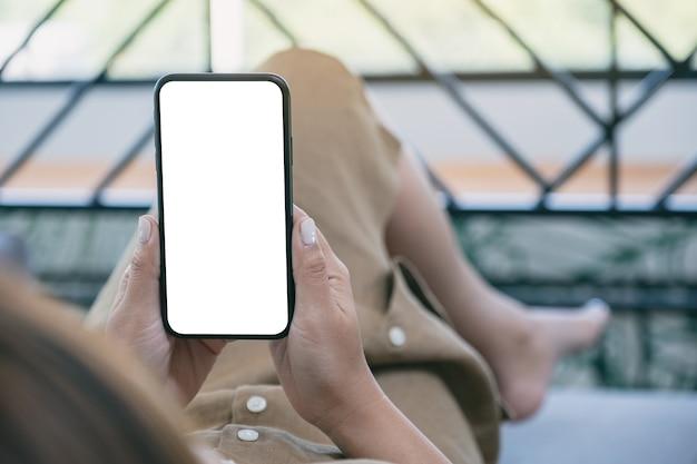 Modellbild einer frau, die schwarzes mobiltelefon mit leerem weißem desktop-bildschirm hält, während im wohnzimmer mit dem gefühl entspannt liegt Premium Fotos