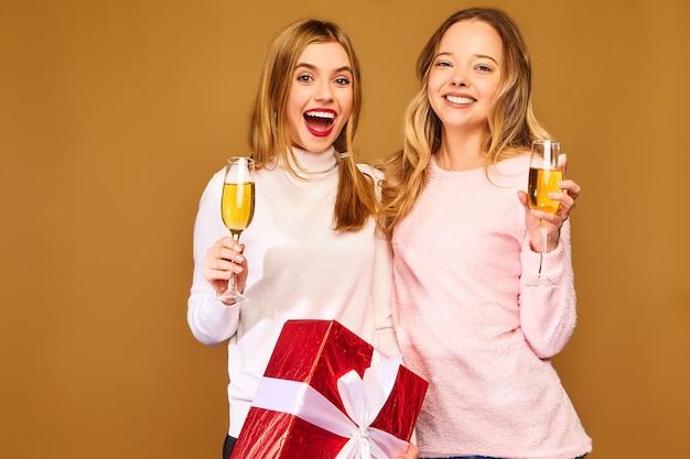 Modelle mit großer geschenkbox, die champagner in gläsern trinken, die neujahr feiern Kostenlose Fotos