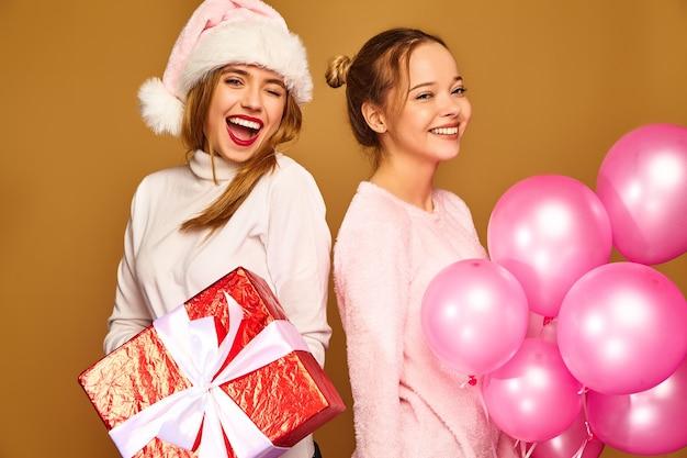 Modelle mit großer geschenkbox und rosa luftballons an weihnachten Kostenlose Fotos