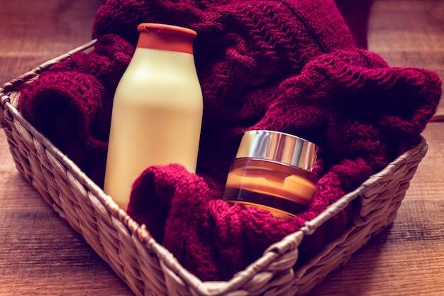 Modelle von flaschen mit körpercreme und shampoo auf einem pullover Premium Fotos