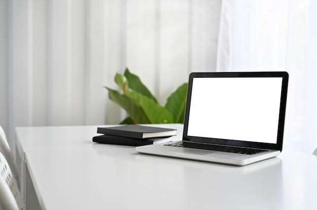 Modelllaptop-computer und notizbuchpapier auf funktionstabelle. Premium Fotos