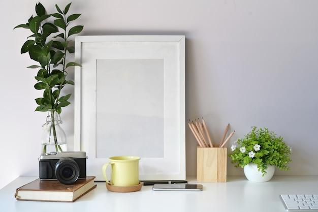 Modellplakatschablone mit weinlesekamera, versorgungen auf weißem schreibtischarbeitsplatz Premium Fotos