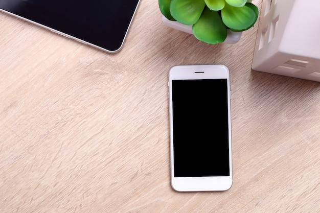 Modellschirm smartphone, tablette und büroartikel auf hölzernem hintergrund Premium Fotos