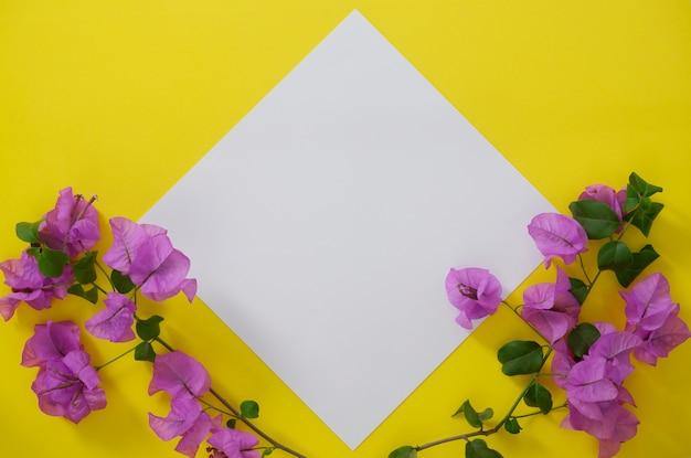 Modellweißbuch mit platz für text oder bild auf gelbem hintergrund und blumen. Premium Fotos