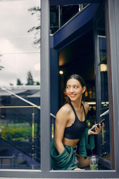 Modemädchen, das in einem sommercafé steht Kostenlose Fotos