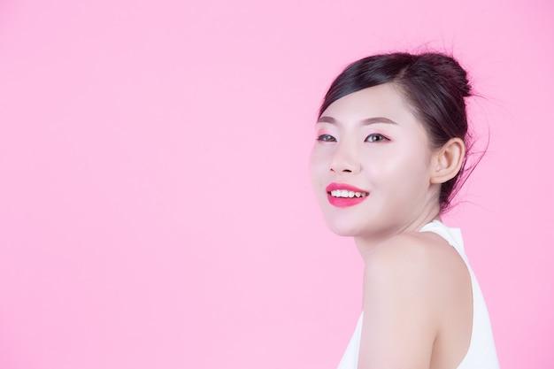 Modemädchen kleiden oben mit handzeichen auf einem rosa hintergrund an. Kostenlose Fotos