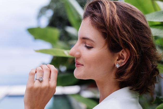 Modeporträt der frau an der tropischen luxusvilla, die weißen stilvollen blazer und schmuck über tropischen blättern trägt Kostenlose Fotos