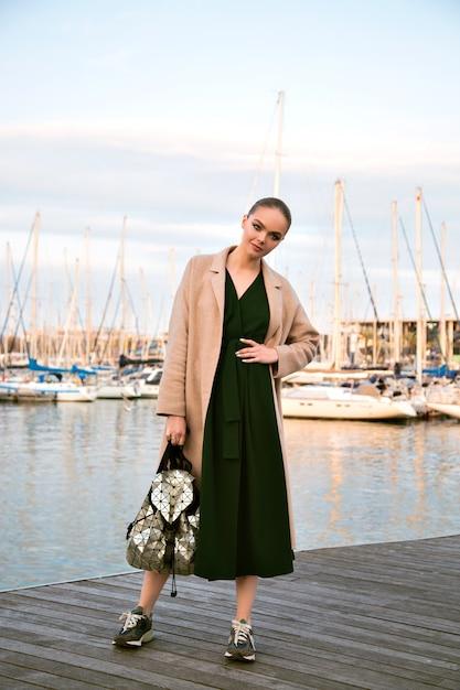 Modeporträt der jungen atemberaubenden eleganten frau, die promenade aufwirft, kleidermantel-turnschuhe und rucksack, luxus-tourist, weiche warme farben trägt. Kostenlose Fotos