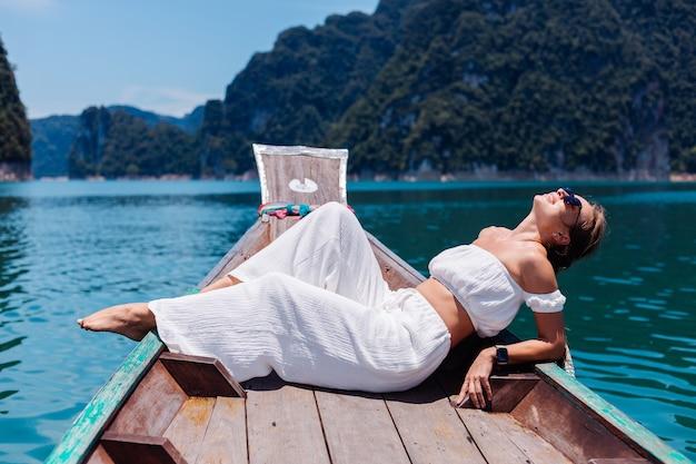 Modeporträt der jungen frau im weißen oberteil und in den hosen im urlaub, auf dem segeln des thailändischen holzboots. reisekonzept. frau im khao sok nationalpark. Kostenlose Fotos