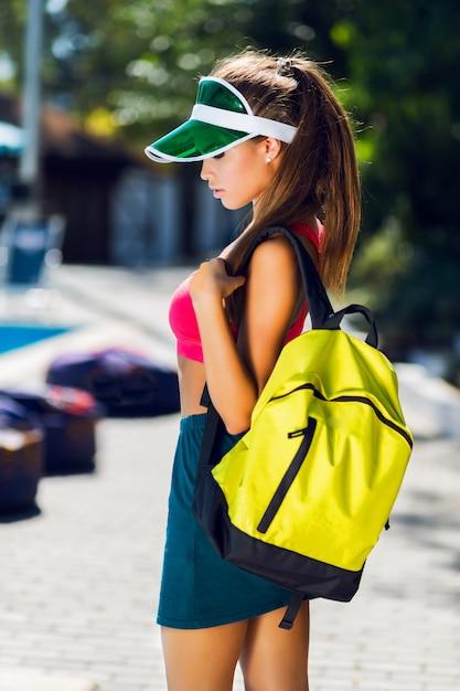 Modeporträt der jungen schönen frau in der stilvollen sportuniform mit neonrucksack und transparentem visier, das draußen im sonnigen sommertag aufwirft. Kostenlose Fotos