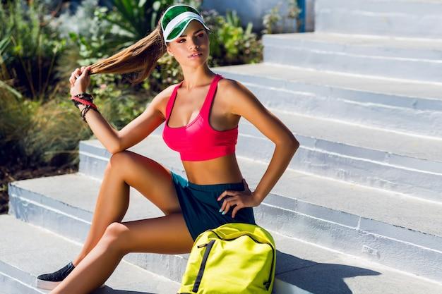 Modeporträt der jungen schönen frau in der stilvollen sportuniform mit neonrucksack und transparentem visier, das nahe turnhalle im sonnigen sommertag aufwirft. Kostenlose Fotos