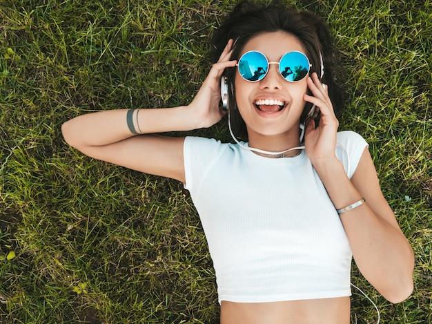 Modeporträt der jungen stilvollen hipsterfrau, die auf dem gras im park liegt. mädchen trägt trendiges outfit. lächelndes modell genießen ihre wochenenden. frau, die musik über kopfhörer hört. draufsicht Kostenlose Fotos