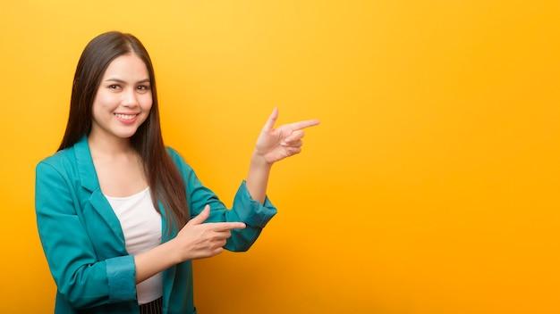 Modeporträt der schönen frau im grünen anzug, der etwas auf ihrer hand auf gelber wand zeigt Premium Fotos