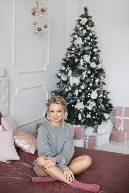 Modeporträt des modellmädchens mit perfektem make-up und frisur drinnen mit weihnachtsbaum am hintergrund. nette blonde frau im kuscheligen strickkleid auf dem bett in für neujahrseinrichtung dekoriert Premium Fotos