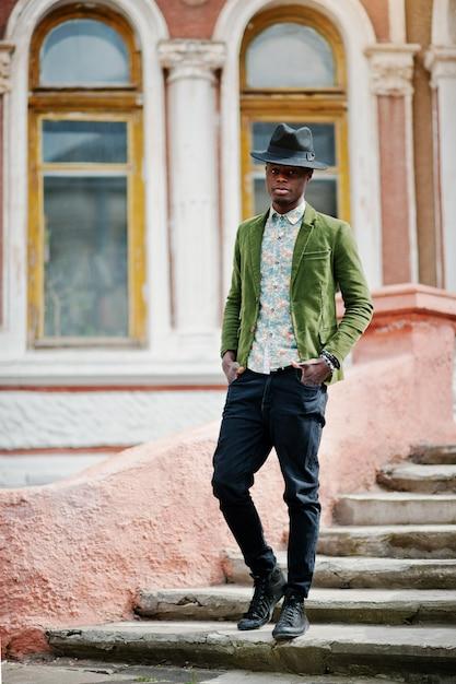 Modeporträt des schwarzafrikanermannes auf grüner samtjacke und schwarzem hut bleiben auf alter villa des treppenhintergrundes. vertikales foto Premium Fotos