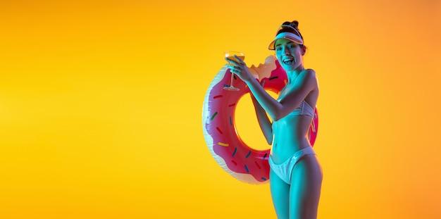 Modeporträt des verführerischen mädchens in der stilvollen badebekleidung, die auf einer hellen gelben wand aufwirft. sommerzeit, strandsaison Kostenlose Fotos
