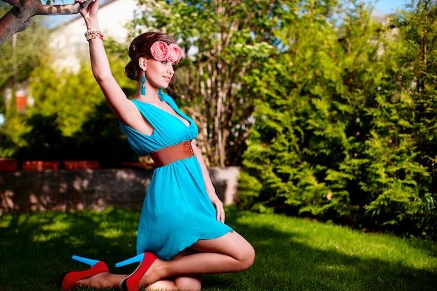 Modeporträt schöner junger weiblicher vorbildlicher damenfrau mit frisur im hellen blauen kleid, das draußen sitzen im grünen gras nahe busch mit blumen im haar aufwirft Kostenlose Fotos