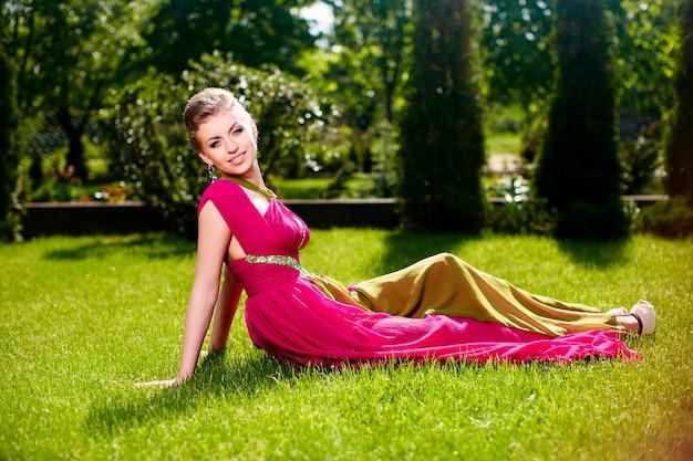 Modeporträt schöner lächelnder weiblicher vorbildlicher damenfrau der junge mit frisur im hellen kleid, das draußen liegen im grünen gras aufwirft Kostenlose Fotos