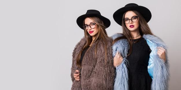 Modeporträt von zwei eleganten frauen, beste freunde, die innen auf grauer wand posieren, die flauschigen wintermantel, schwarzen freizeithut tragen. moderne kleidung. schwestern gehen. Kostenlose Fotos