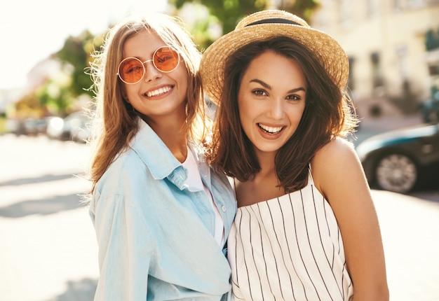 Modeporträt von zwei jungen lächelnden stilvollen hippie-brünetten- und blonden frauenmodellen im sonnigen sommertag in der hipster-kleidung, die auf dem straßenhintergrund aufwirft Kostenlose Fotos