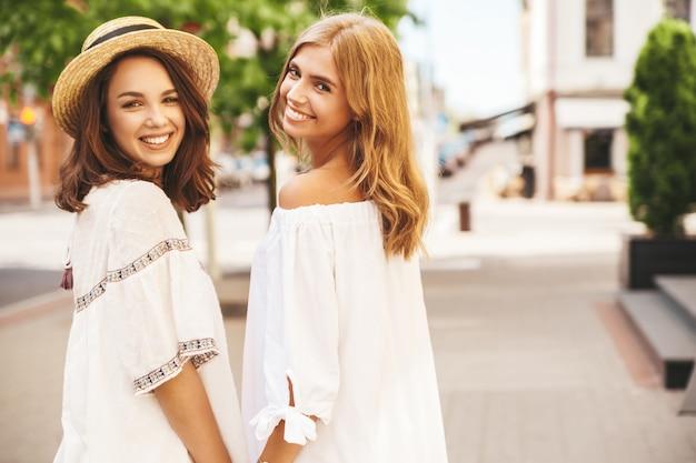 Modeporträt von zwei jungen stilvollen hippie-brünetten- und blonden frauenmodellen ohne make-up im sonnigen sommertag in der weißen hipster-kleidung, die aufwirft. dreh dich um Kostenlose Fotos