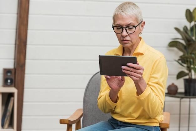 Moderne ältere frau, die eine tablette hält Kostenlose Fotos