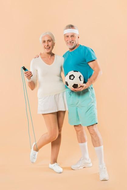 Moderne ältere paare mit springseil und fußball Kostenlose Fotos