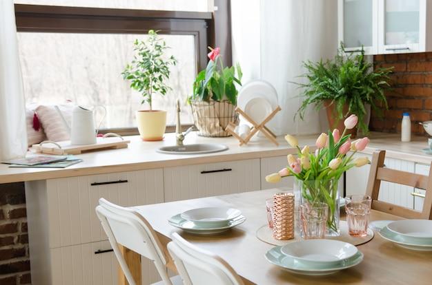 Moderne designküche. esstischgedeck mit blumenvase Premium Fotos