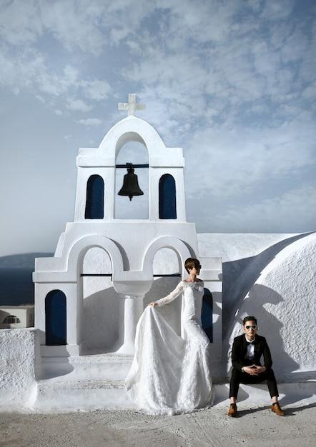 Moderne elegante jungvermähltenpaare an der alten weißen kirche im dorf von oia auf der insel von santorini, griechenland Premium Fotos