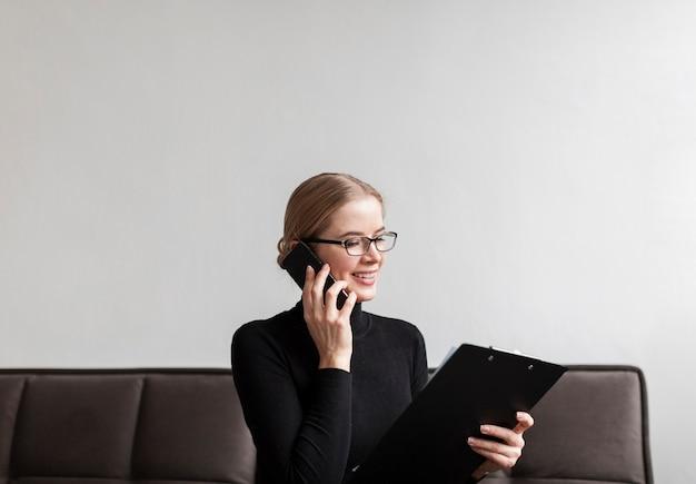 Moderne frau des smiley, die über telefon spricht Kostenlose Fotos