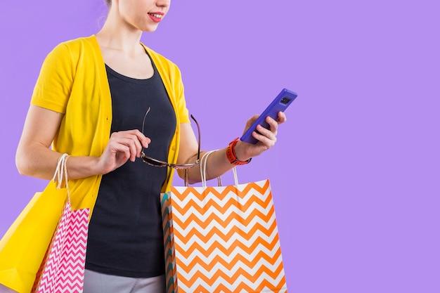 Moderne frau, die mobiltelefon mit dem halten der bunten papiertüte und der brillen verwendet Kostenlose Fotos