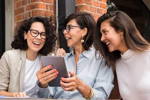 Moderne frauen des smiley, die auf einer tablette schauen Kostenlose Fotos