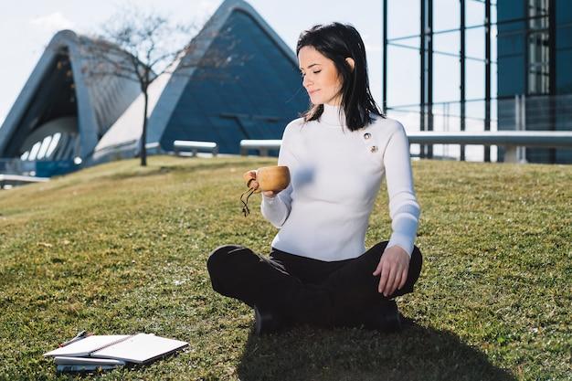 Moderne geschäftsfrau, die auf hügel sich entspannt Kostenlose Fotos