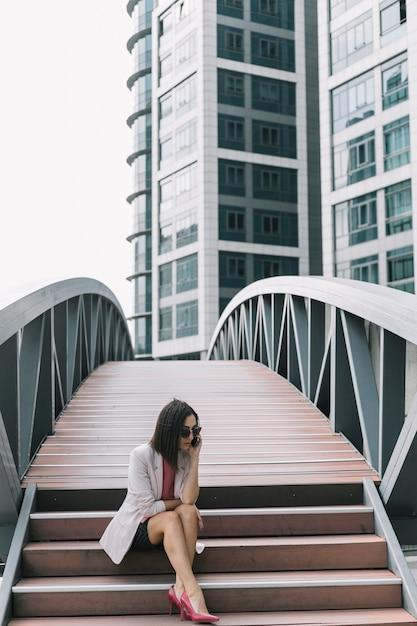 Moderne geschäftsfrau, die auf treppenhaus unter verwendung des handys sitzt Kostenlose Fotos