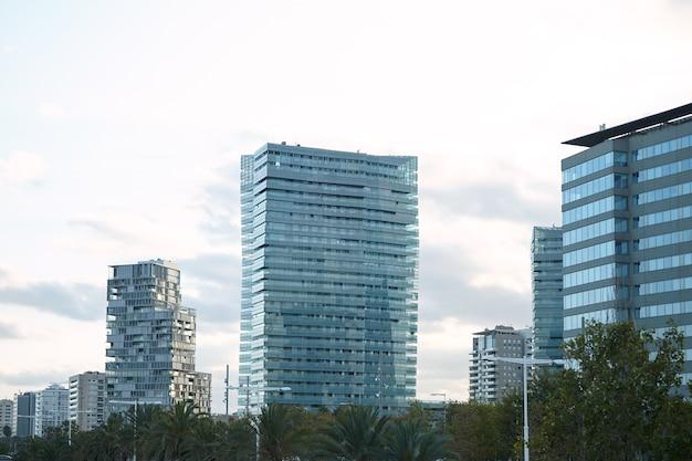 Moderne glas- und betonstadtgebäude minuten nach sonnenuntergang gegen klaren weißen himmel Kostenlose Fotos