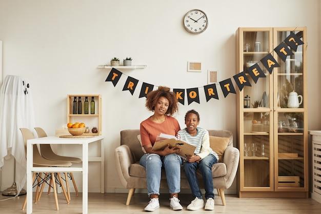 Moderne junge erwachsene frau, die zeit mit ihrem sohn verbringt, der zusammen auf sofa im wohnzimmer sitzt, verziert für halloween und lesebuch, kopienraum Premium Fotos