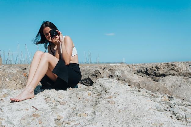 Moderne junge frau, die foto mit der kamera sitzt auf felsen an draußen macht Kostenlose Fotos