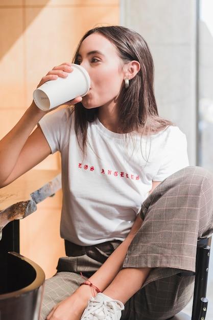 Moderne junge frau, die im café trinkt den kaffee sitzt Kostenlose Fotos