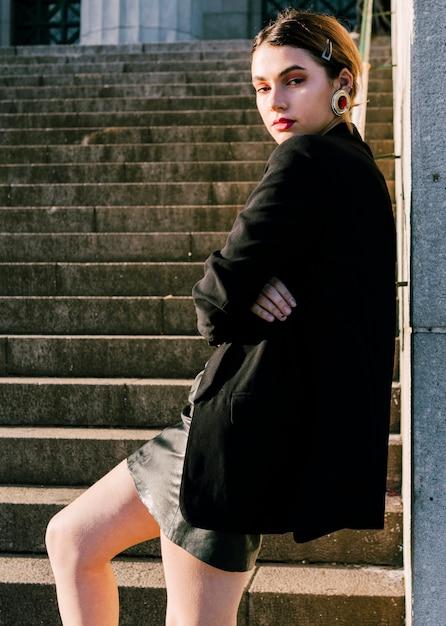 Moderne junge frau, die vor treppenhaus mit dem arm gekreuzt steht Kostenlose Fotos