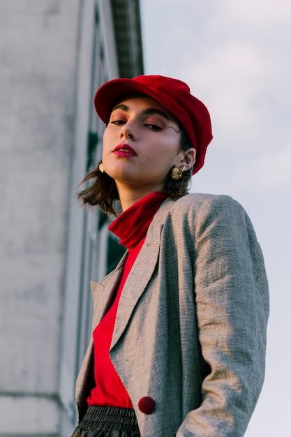 Moderne junge frau mit der roten kappe, die kamera betrachtet Kostenlose Fotos