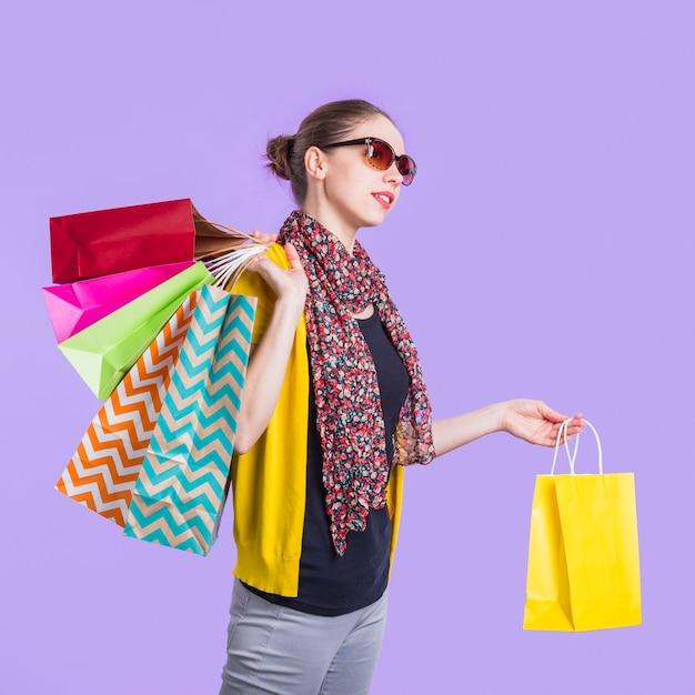 Moderne junge frau mit einkaufstasche über purpurrotem hintergrund Kostenlose Fotos