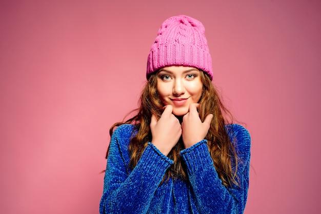 Moderne junge frau, welche die blaue strickjacke und rosa hut aufwirft, lustigen gesichtsausdruck machend trägt. Premium Fotos