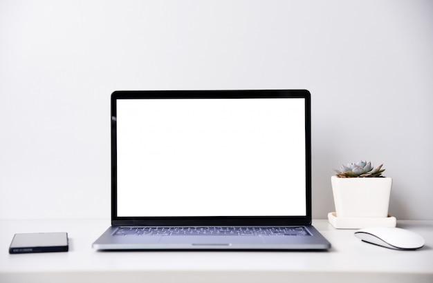 Moderne laptop-computer des leeren bildschirms mit maus und pflänzchen, arbeitsbereichdesktop Premium Fotos