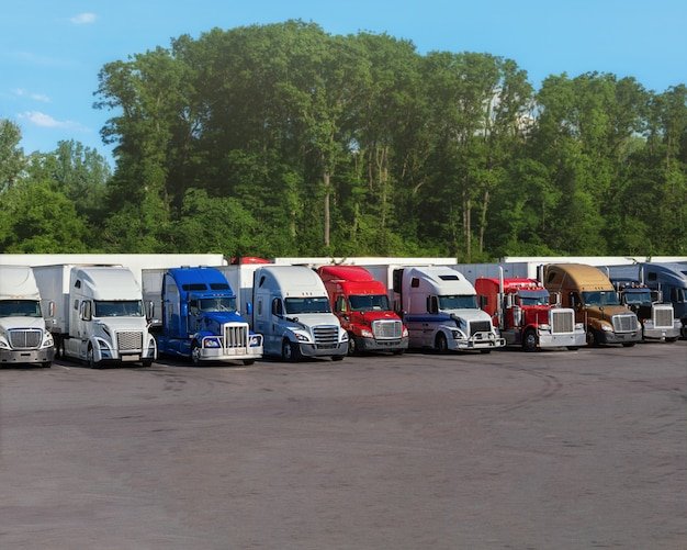 Moderne lkws in verschiedenen farben und modellen, die verschiedene arten von handelsgütern transportieren, stehen in einer reihe auf dem parkplatz für lkw-haltestellen, damit der lkw-fahrer laut logbuch ruhen kann. Premium Fotos
