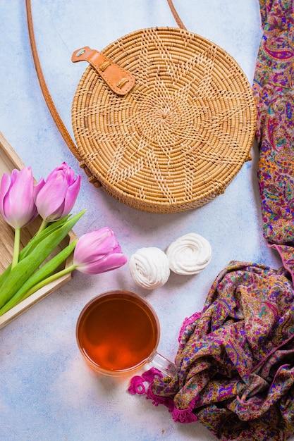 Moderne rattantasche, tasse tee, tulpen und schal auf hellem hintergrund. Premium Fotos