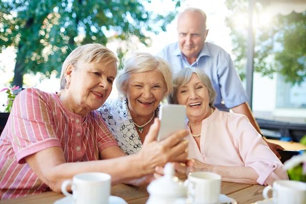 Moderne senioren, die foto von selbst machen Kostenlose Fotos