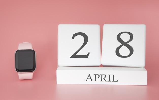 Moderne uhr mit würfelkalender und datum 28. april auf rosa hintergrund. konzept frühlingszeit urlaub. Premium Fotos